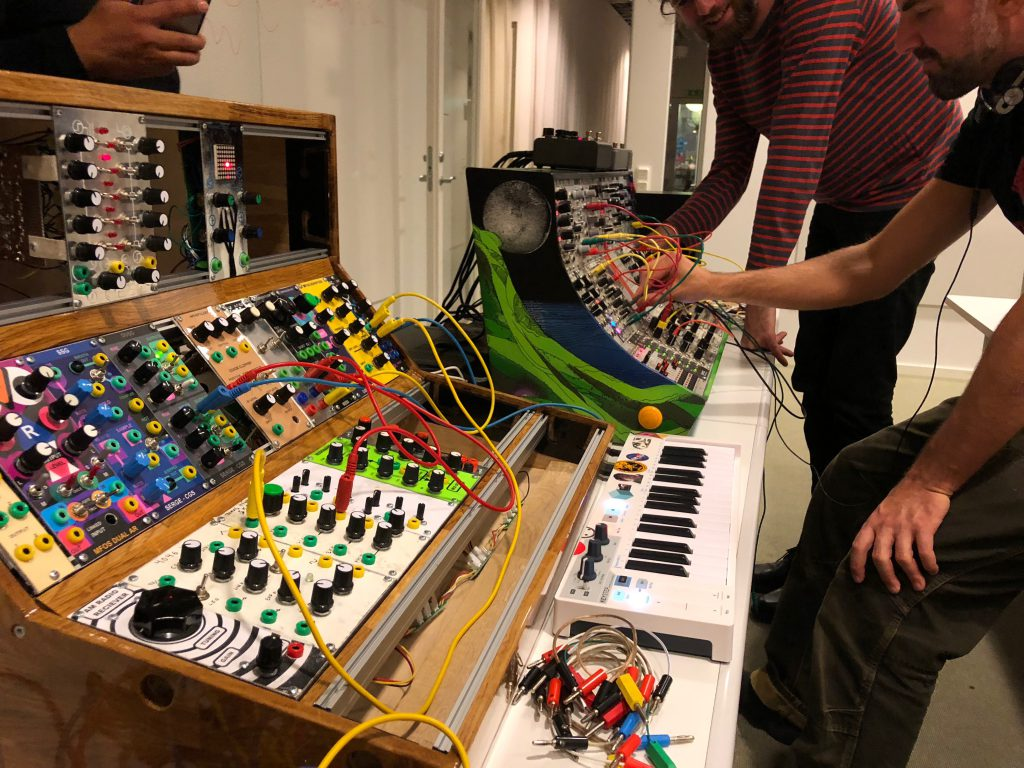 Modular synthesizers in their cases, and operators smiling